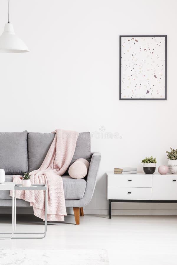 Affiche moderne sur un mur blanc, un sofa gris avec la couverture et un cabine photo libre de droits