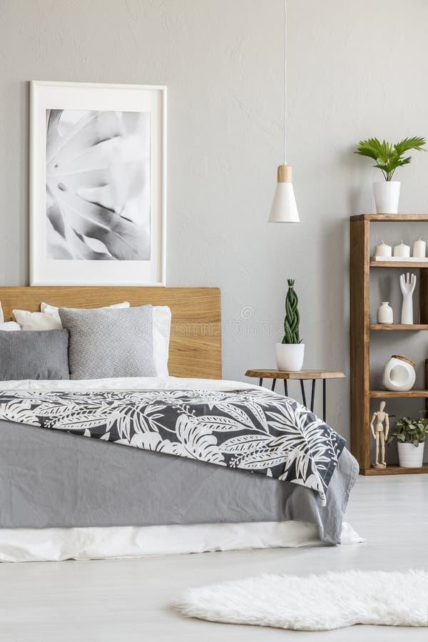 Affiche op houten hoofdeinde van bed met grijze bladen in helder bed royalty-vrije stock afbeeldingen