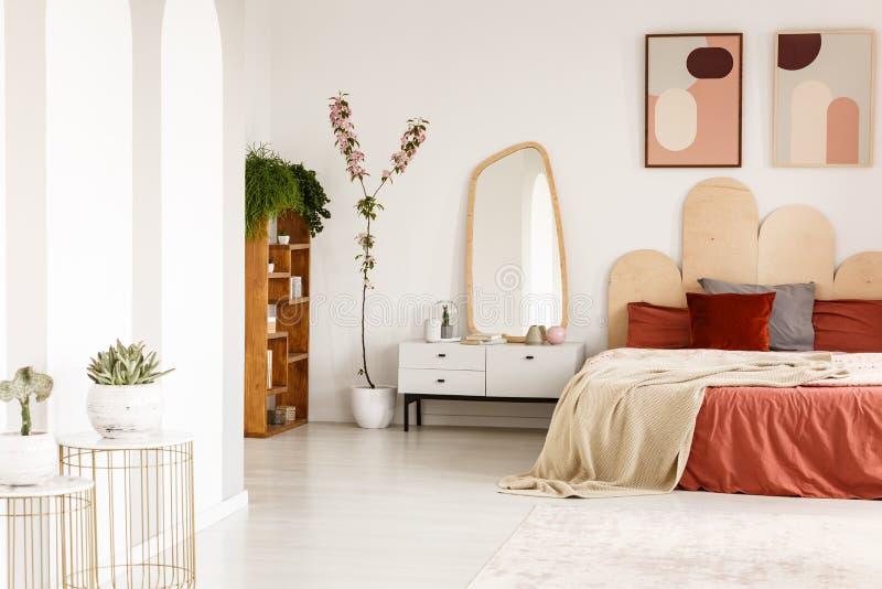 Affiches au-dessus de lit rouge avec la couverture dans l'intérieur spacieux de chambre à coucher photographie stock libre de droits