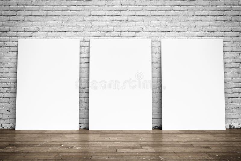 Affiches blanches sur le plancher de mur de briques et en bois photographie stock libre de droits