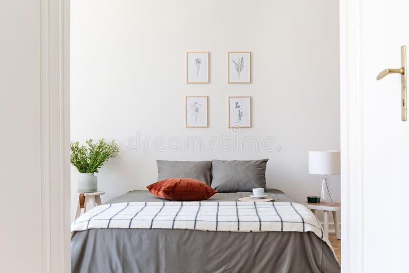 Affiches boven grijs bed met gevormd algemeen en rood binnen hoofdkussen stock fotografie