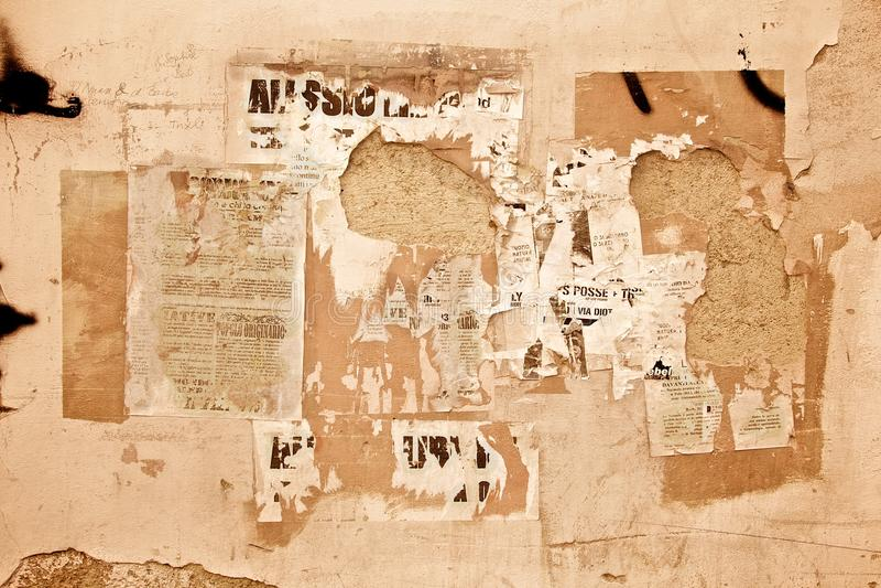 Affiches fanées sur le mur photographie stock