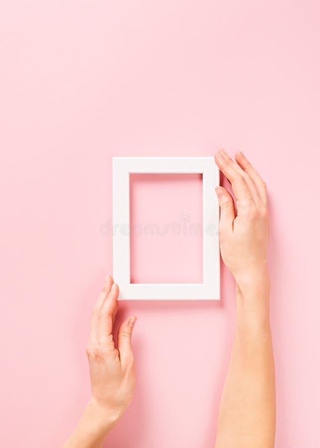 Affiches faux vers le haut de et cadre de fond ou avec la main sur le rose photographie stock