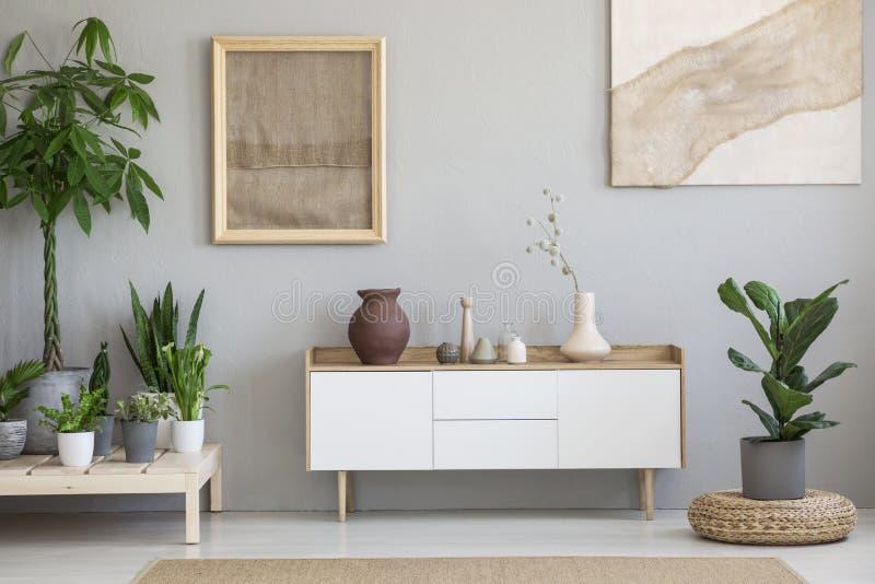 Affiches op grijze muur boven witte kast in woonkamerinterio royalty-vrije stock foto's
