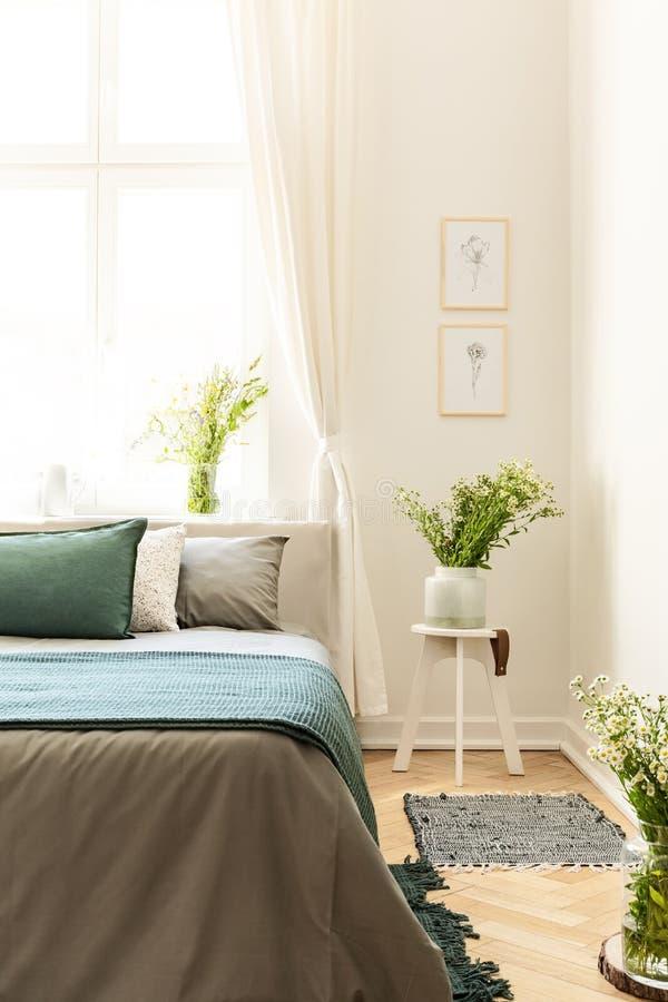 Affiches op witte muur boven bloemen op lijst naast grijs en gr. royalty-vrije stock fotografie