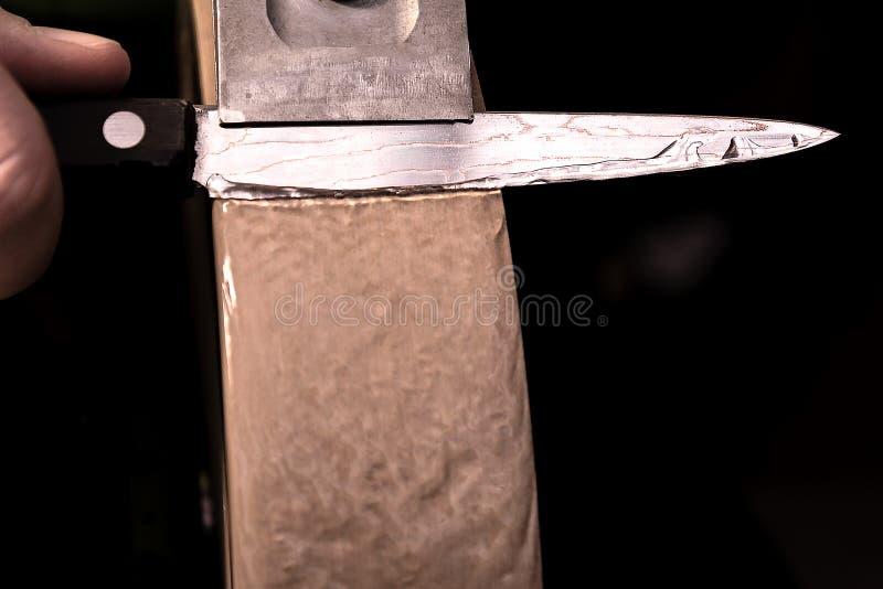 Affilatura del coltello d'acciaio di Damasco su una pietra per affilare dell'acqua immagine stock