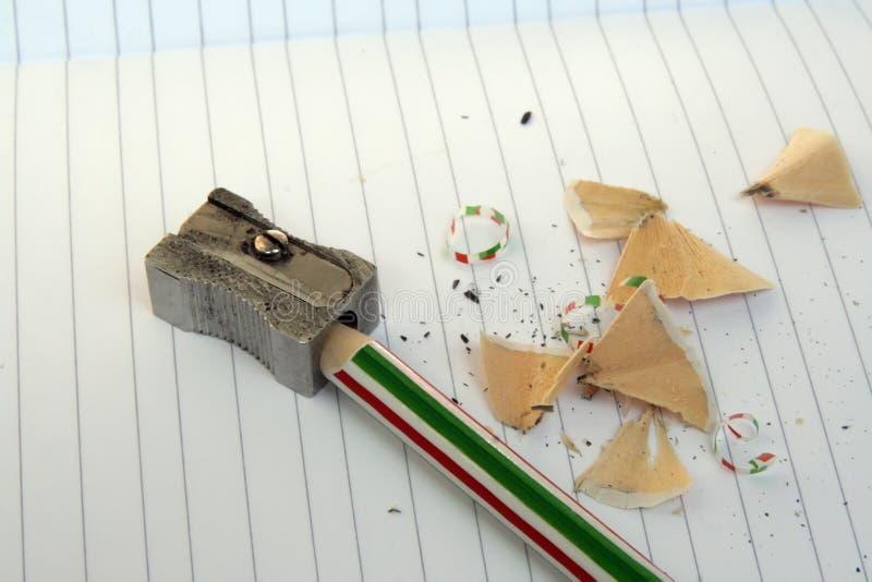 Affilatura della matita su un taccuino nelle linee fotografia stock libera da diritti