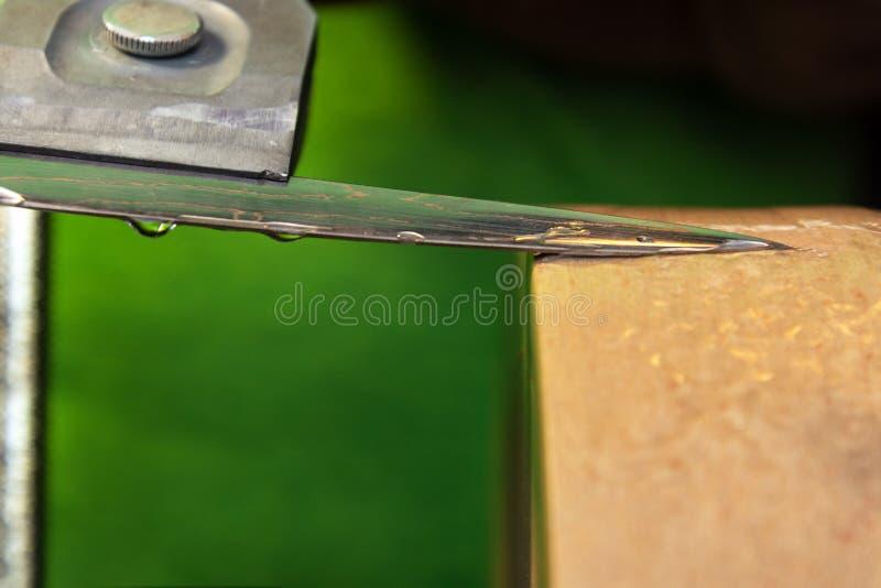 Affilatura della punta di un coltello su una macina dell'acqua fotografie stock
