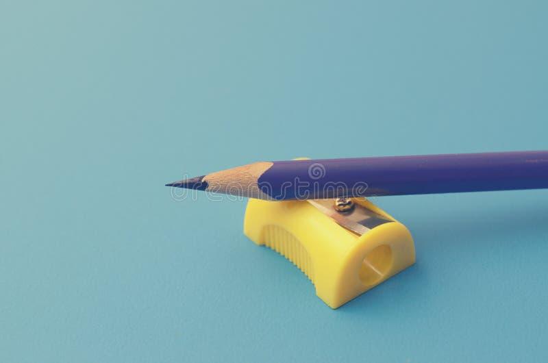 Affili le matite colorate con un'affilatrice fotografia stock libera da diritti
