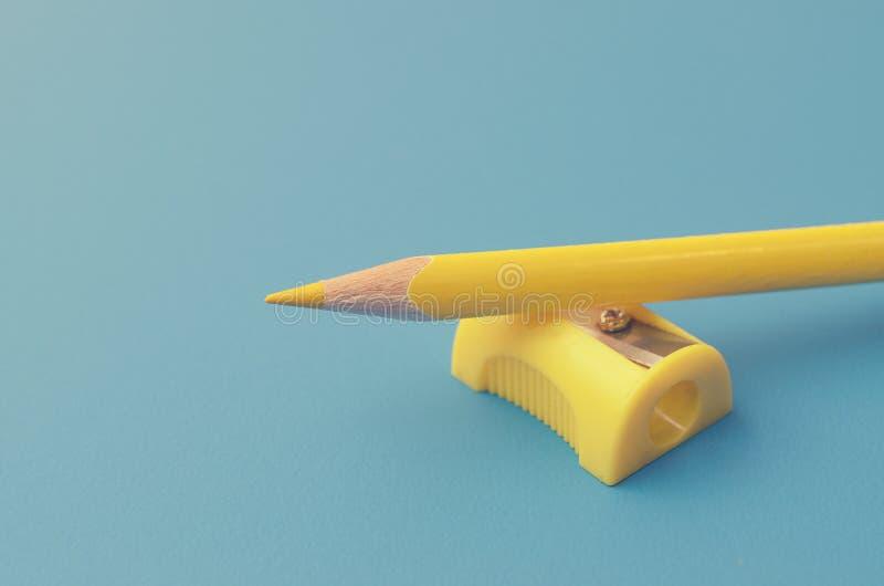Affili le matite colorate con un'affilatrice fotografie stock libere da diritti