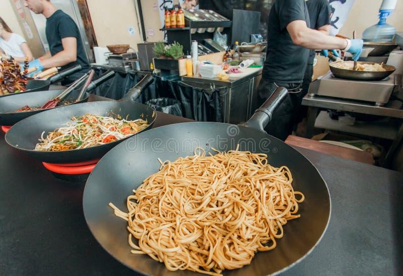 Affinez les nouilles sèches dans la casserole du café asiatique de prêt-à-manger pendant le festival extérieur populaire de nourr photos stock