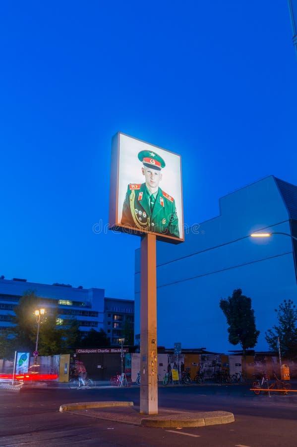 Affisch av rysssoldaten på Checkpoint Charlie på natten arkivfoton