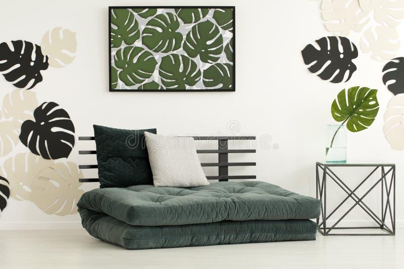 Affisch av sidor ovanför futon med kuddar i det moderna sovrummet int royaltyfri fotografi