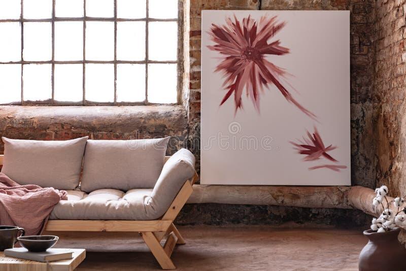 Affisch bredvid fönster i industriell vardagsruminre med den gråa träsoffan med filten arkivbilder