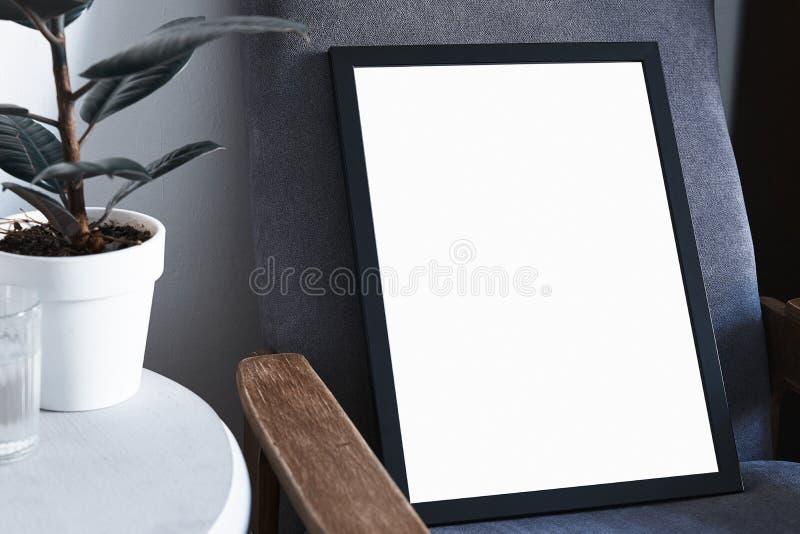Affisch i svart ram i den nordiska stilfulla moderna inre, grå fåtölj, fikus, vardagsrum Töm utrymme för designorientering royaltyfri foto