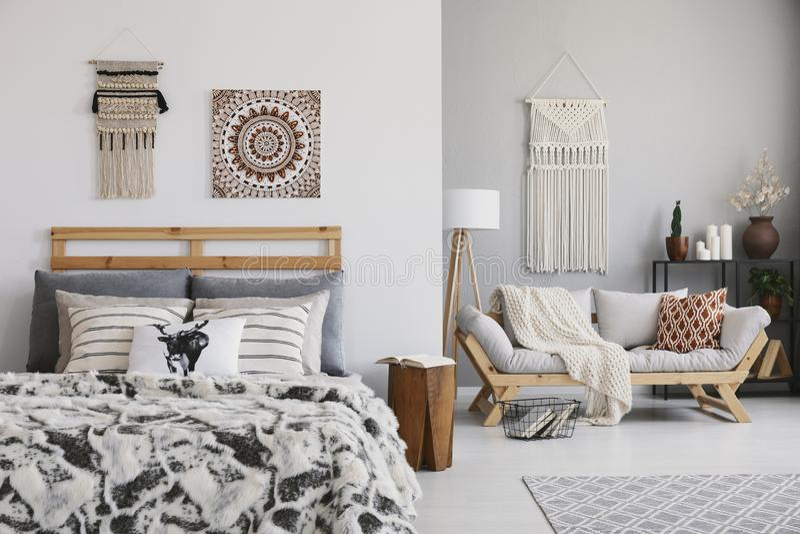Affisch och dekor ovanför mönstrad säng i plan inre för hygge med kuddar på träsoffan royaltyfri fotografi