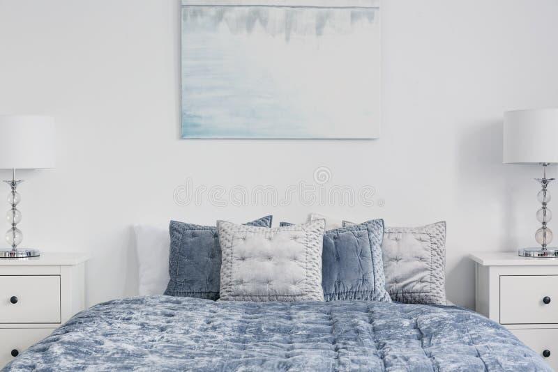 Affisch ovanför blå säng med kuddar i det vita enkla sovrummet som är inre med lampor på kabinetter Verkligt foto royaltyfri bild