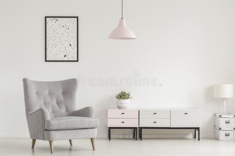 Affisch ovanför den grå färgfåtöljen och lampan i den vita vardagsruminterioen royaltyfria foton