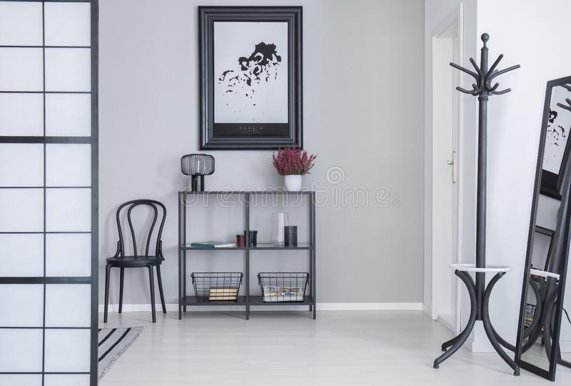 Affisch ovanför hyllor med blommor och lampan i den vita enkla korridorinre med kuggen och svart stol royaltyfri foto