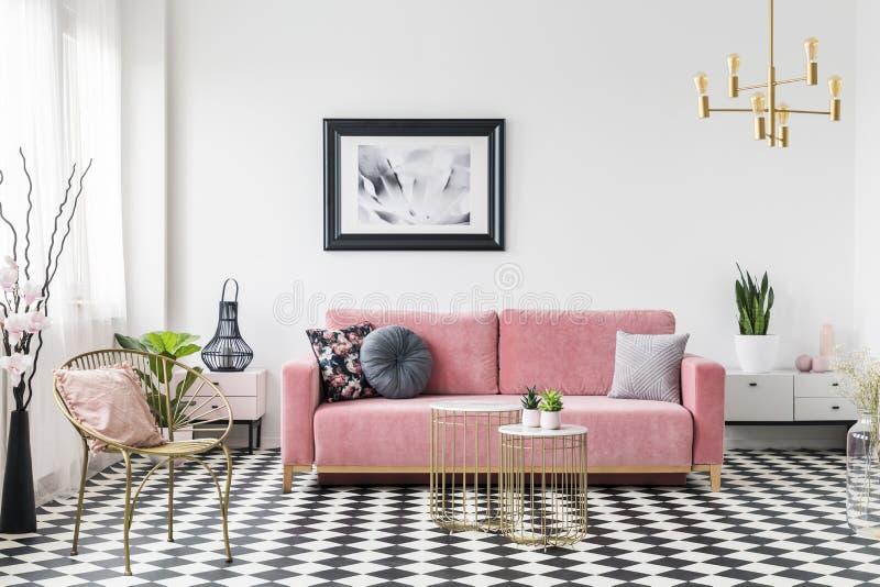 Affisch ovanför rosa färgsoffan i vardagsruminre med den guld- fåtöljen på rutigt golv Verkligt foto arkivfoton