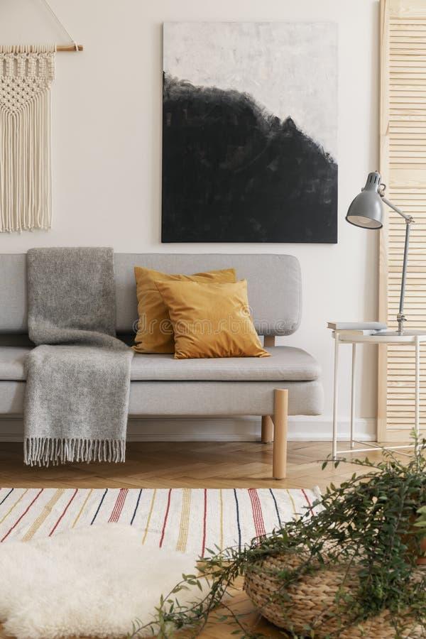 Affisch ovanför soffan med bruna kuddar och den gråa filten arkivbilder
