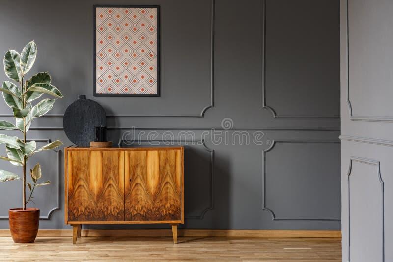 Affisch ovanför träkabinettet bredvid fikus i vardagsruminterio royaltyfri foto