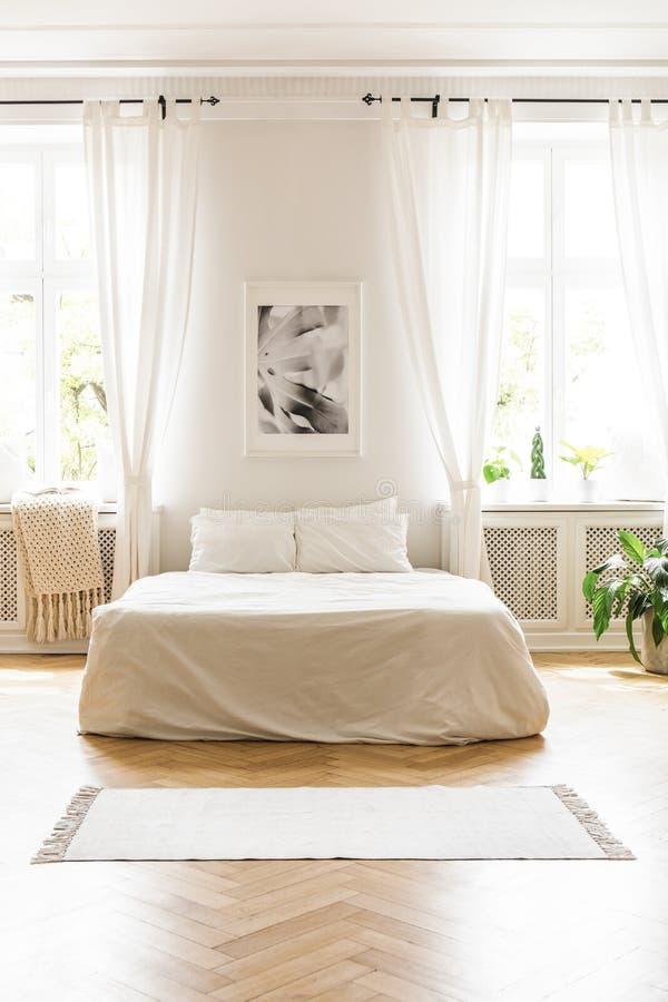 Affisch ovanför vitsäng i minsta sovruminre med förhängear a arkivbilder