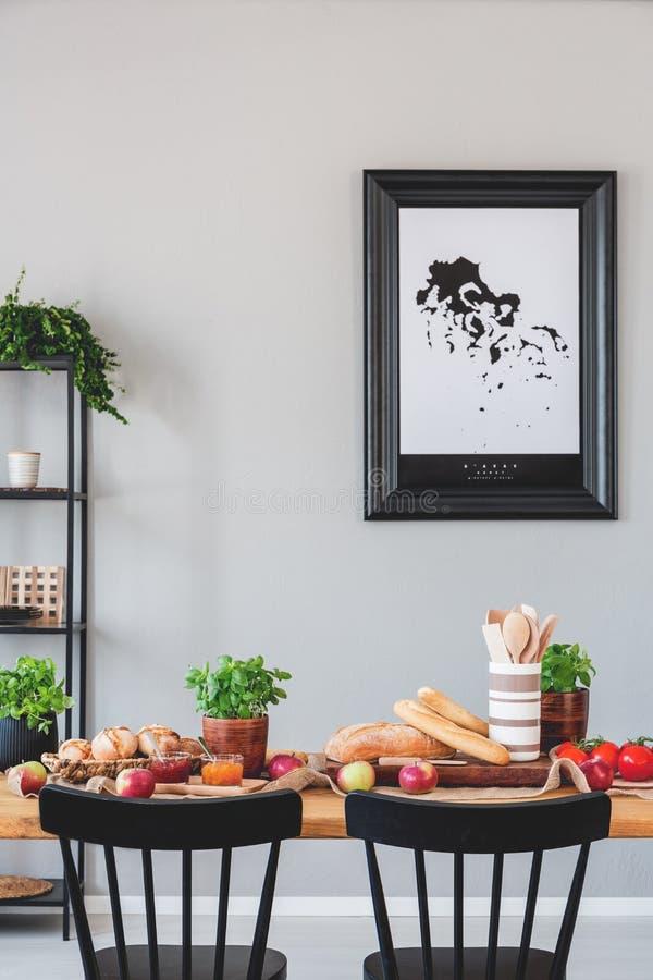 Affisch på den gråa väggen i matsal som är inre med svarta stolar på trätabellen med mat arkivbilder