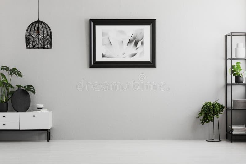 Affisch på den gråa väggen i tom vardagsruminre med växter, lampan och skåpet Ställe för din soffa Verkligt foto royaltyfri bild