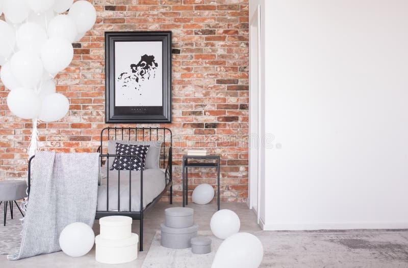 Affisch på väggen för röd tegelsten ovanför säng i inre med kopieringsutrymme och ballonger Verkligt foto royaltyfri bild
