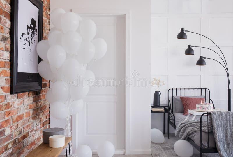 Affisch på väggen och ballonger för röd tegelsten i sovruminre Verkligt foto arkivbilder