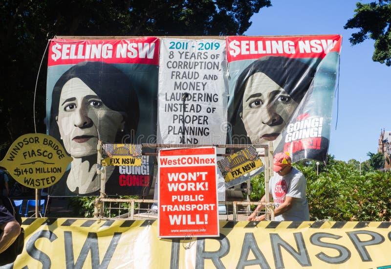 Affischen av ledaren av det frisinnade partiet, är Gladys Berejiklian, vid personen som protesterar för besparingen NSW, stoppar  arkivfoton