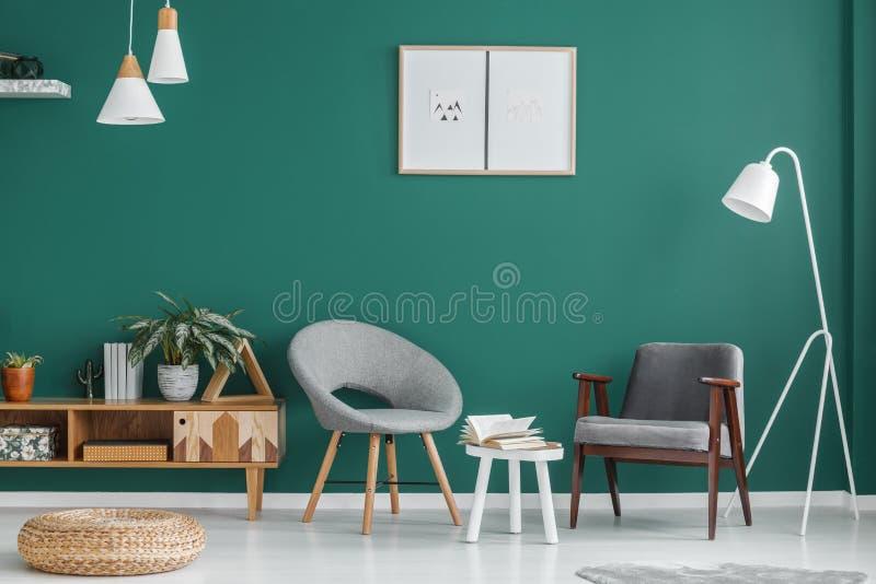 Affischer i grön vardagsrum royaltyfri foto