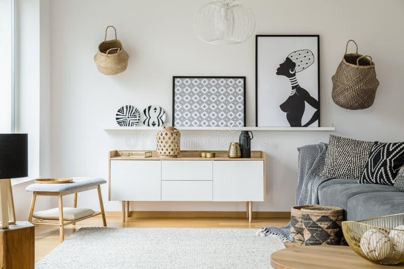 Affischer och plattor ovanför träskåp i bohovardagsrum int royaltyfri bild