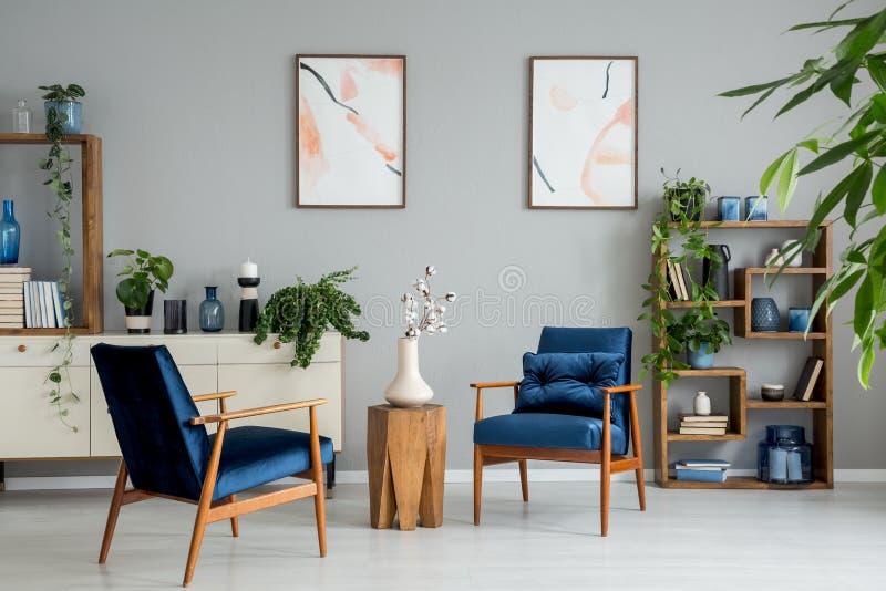 Affischer och växter i ljus vardagsruminre med marinblåa fåtöljer och blommor Verkligt foto arkivfoton