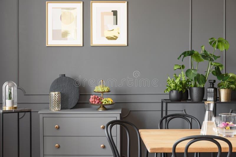 Affischer ovanför grå färgkabinettet i mörk matsalinre med plommoner arkivbilder