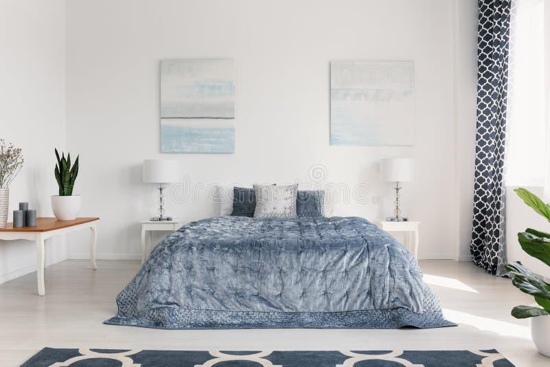 Affischer ovanför säng med blåa ark i den vita sovruminre med lampor och växten på tabellen Verkligt foto fotografering för bildbyråer