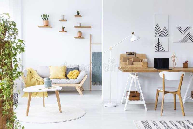 Affischer ovanför skrivbordet med bärbara datorn i den vita vardagsruminre med soffan och trätabellen Verkligt foto royaltyfri bild