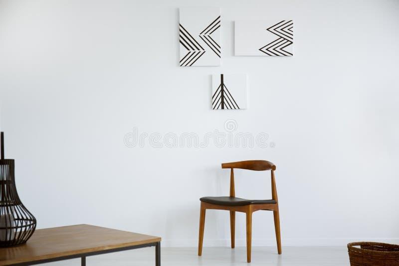 Affischer på den vita väggen ovanför trästol i minsta vardagsruminre med tabellen Verkligt foto fotografering för bildbyråer