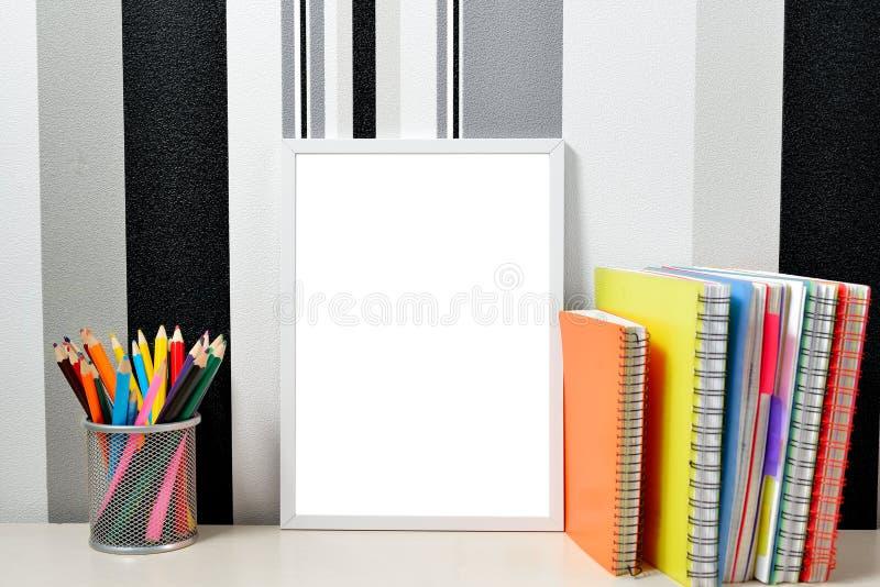 Affischramåtlöje upp mall med kulöra anteckningsböcker och kan med blyertspennor på trätabellen fotografering för bildbyråer