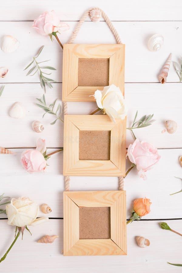 Affischrammodell, bästa sikt, rosa rosor på vit träbakgrund Den lyckliga mannen tycker om på ferier på havet Lekmanna- lägenhet k arkivfoton