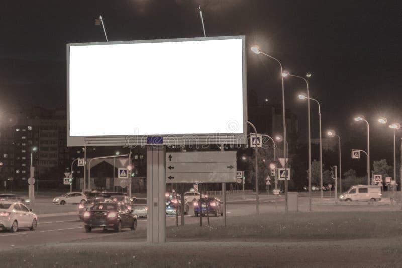 Affischtavla i nattstaden på kanten av gatan annonsering royaltyfria foton