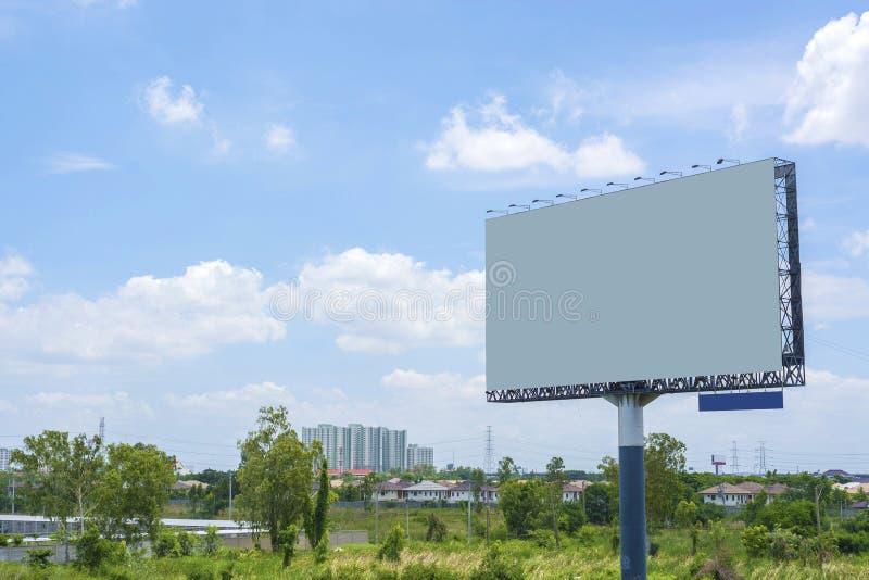 Affischtavla med den tomma skärmen med blå molnig himmel royaltyfri foto