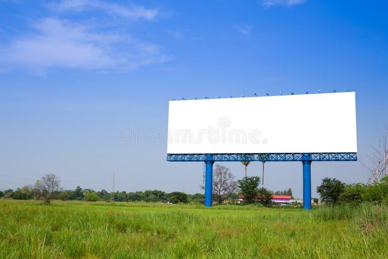 Affischtavla med den tomma skärmen, mot blå molnig himmel royaltyfri foto