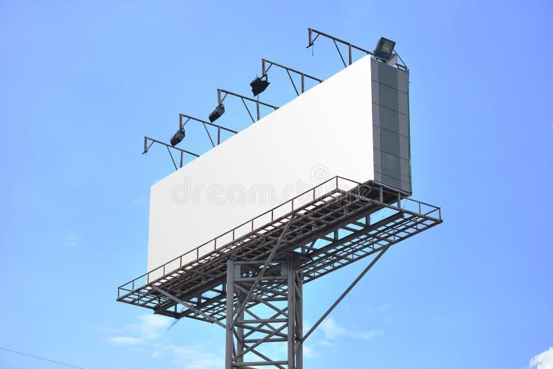 Affischtavla med den tomma skärmen, mot blå molnig himmel arkivfoto