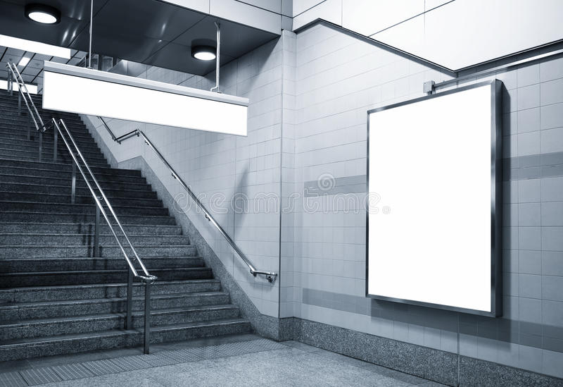 Affischtavla och riktningssignageåtlöje upp i gångtunnel med trappa arkivbild