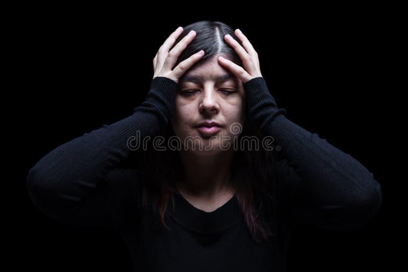 Afflitto, donna tenenti la testa con le mani, su un fondo nero o scuro fotografia stock libera da diritti