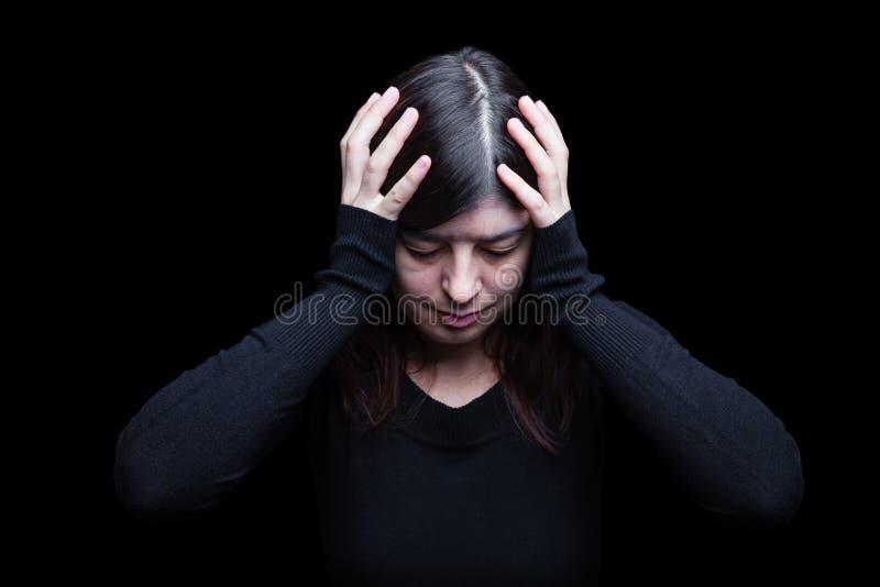 Afflitto, donna tenenti la testa con le mani, su un fondo nero o scuro fotografia stock