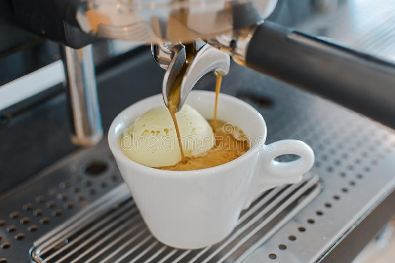 Affogato coffee with ice cream on a ceramic cup with coffee pouring from espresso machine royalty free stock images