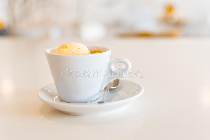 Affogato coffee with ice cream in a ceramic cup on a white wooden table royalty free stock photography